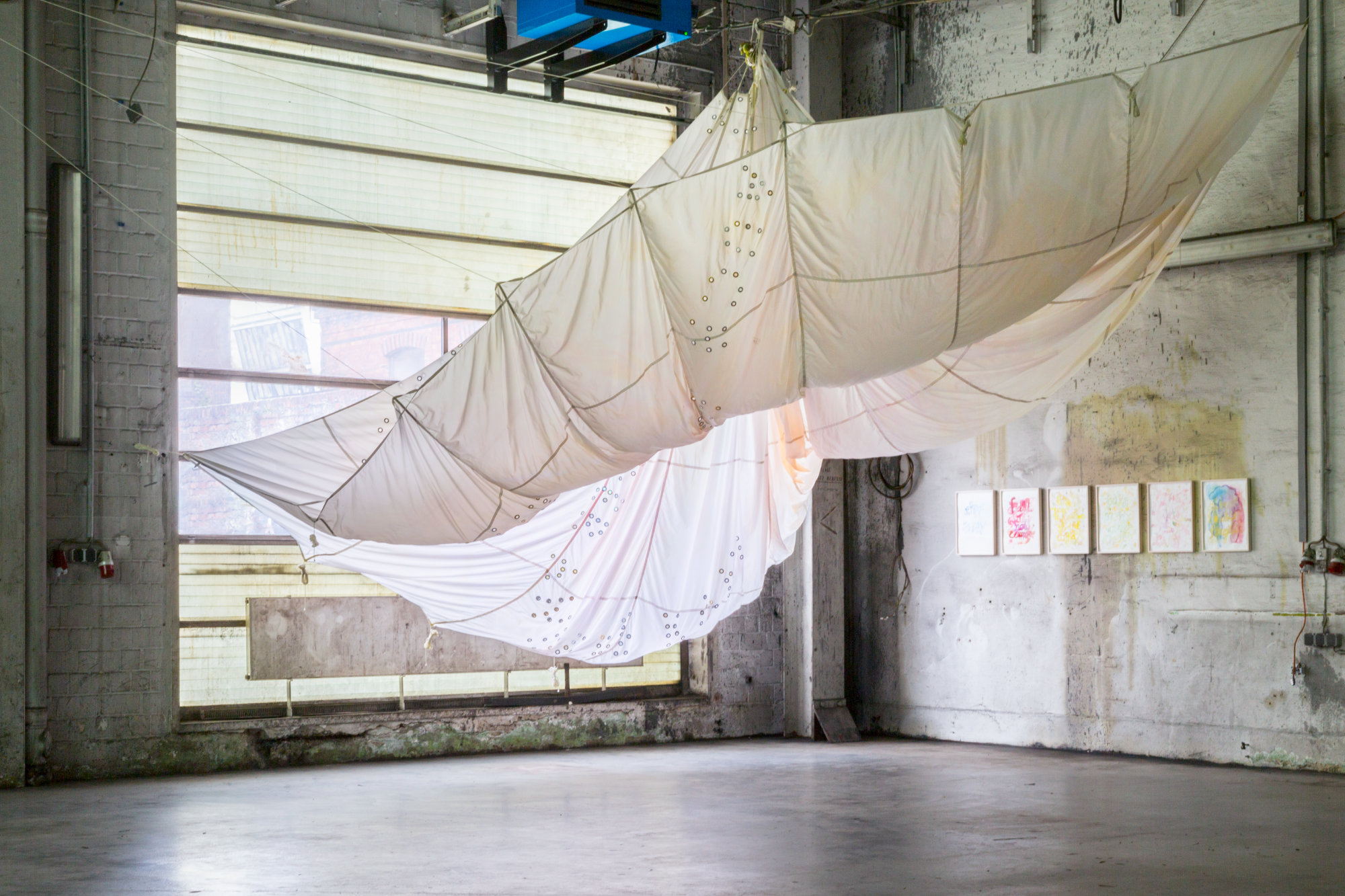 <p>Installation view Markues, <i>Ronald M. Schernikau Fallschirm, </i>ink and eyelets on parachute, dimensions variable, from the series <i>Pressure on Boys,</i> 2018</p>