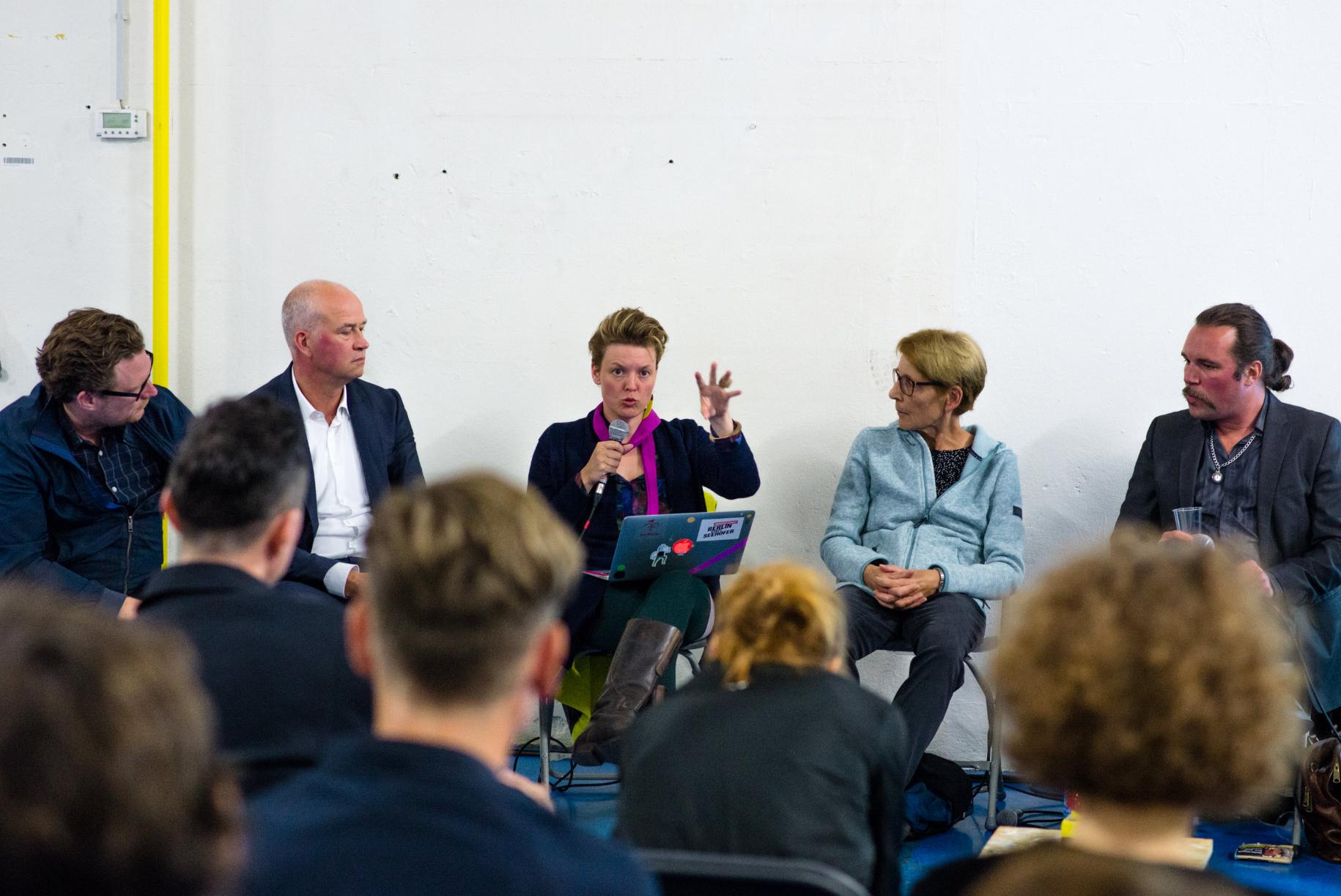 """<p><b>How to breathe in a bubble?</b><b><br /> </b><b>Experimentelles Panel zur Stadtentwicklung </b>mit Marco Schmitt (Performancekünstler und systemischer Coach), Martin Schwegmann (Stadtforscher und Atelierbeauftragter des bbk), Zoe Claire Miller (Künstlerin, Mitgründerin Berlin Art Prize, Sprecherin bbk berlin), Andreas Krüger (Belius GmbH), Alexandra von Stosch (Artprojekt Unternehmensgruppe), Cornelia Wagner (Oranostra Verbund), Sandra Meireis (freie Architekturtheoretikerin), MdA Katalin Gennburg (Sprecherin für Stadtentwicklung, Tourismus und Smart City, Die Linke), Sven Lemiss (Geschäftsführung BIM)</p> <p><i>""""Everything is gentrification now"""" but Richard Florida isn't sorry</i>. Die Stadt wird teurer und enger, manche gewinnen daraus, andere verlieren. Marco Schmitt versuchte an diesem Abend den sozioökonomischen Komplex von Gentrifizierung am Beispiel von Kreuzberg mit Beteiligten der Kunst, Politik und Bauwirtschaft in einer von ihm entwickelten Methode des COA CHING zu entwirren. Dabei brachte er von Betroffenen und Verantwortlichen gleichsam in Erfahrung, welche (moralischen) Handlungsspielräume möglich sind, wenn der urbane Raum von Preisdruck und Knappheit eingeholt wird.</p>"""