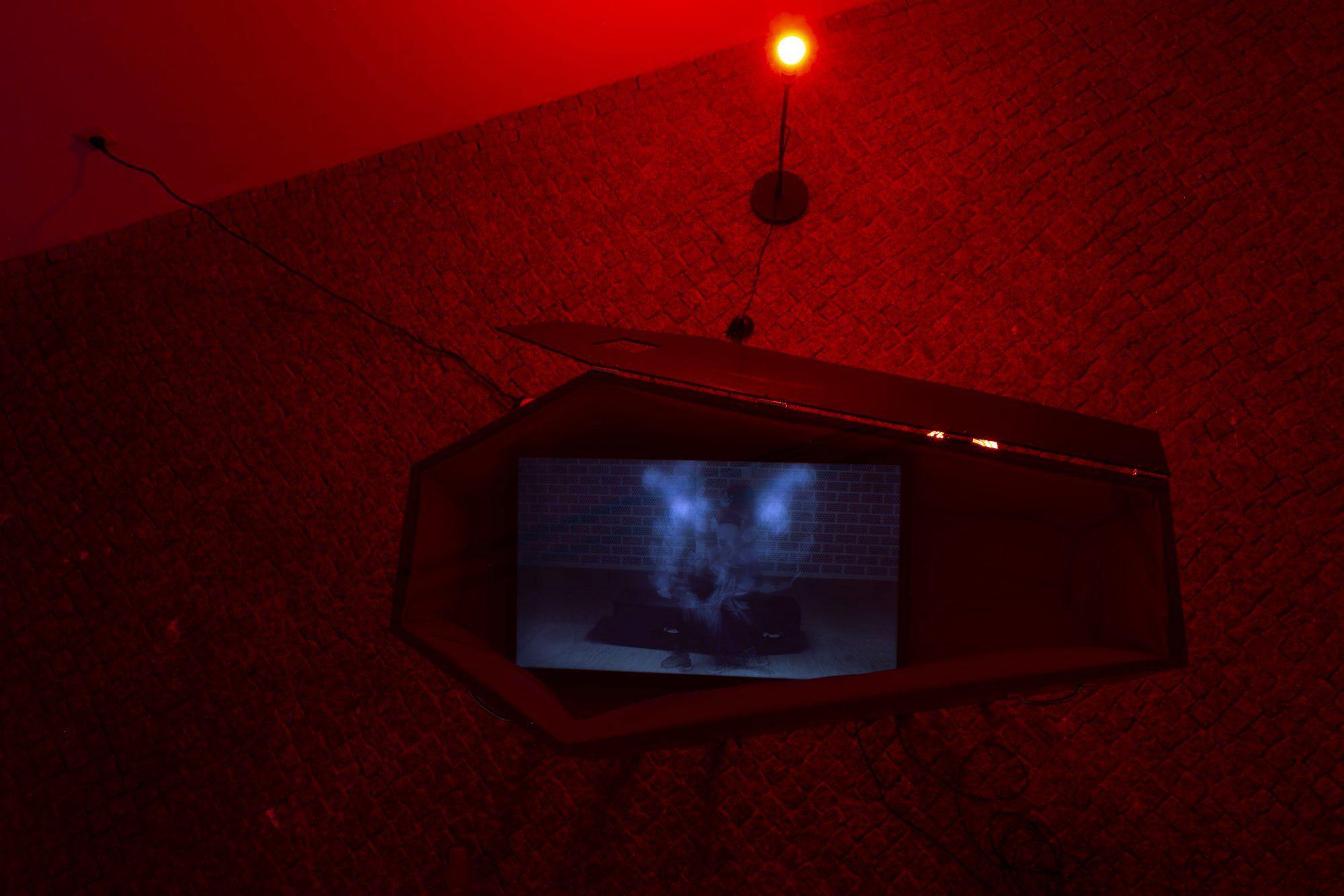"""<p>Esteban Rivera Ariza, """"Hören sie, die Kinder der Nacht, wie sie Musik machen"""", 2019, Videoinstallation im Sarg, Detail der Ausstellung, Foto: Anastasia Muna</p>"""